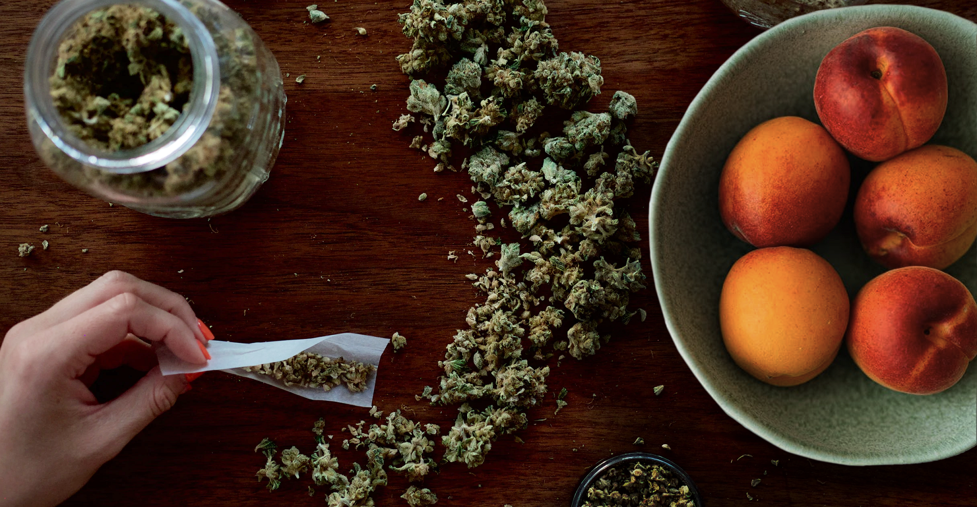 A pile of peach fuzz cannabis strain with a joint being rolled next to a bowl of peaches