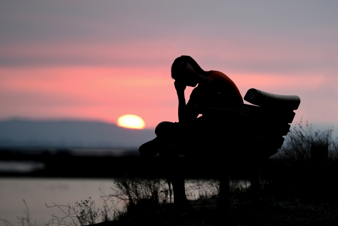 A depressed man sits on a bench in front of the water