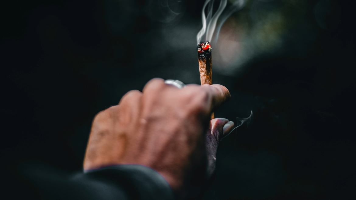 A man holds a perfectly lit joint after showing his friend how to light a joint
