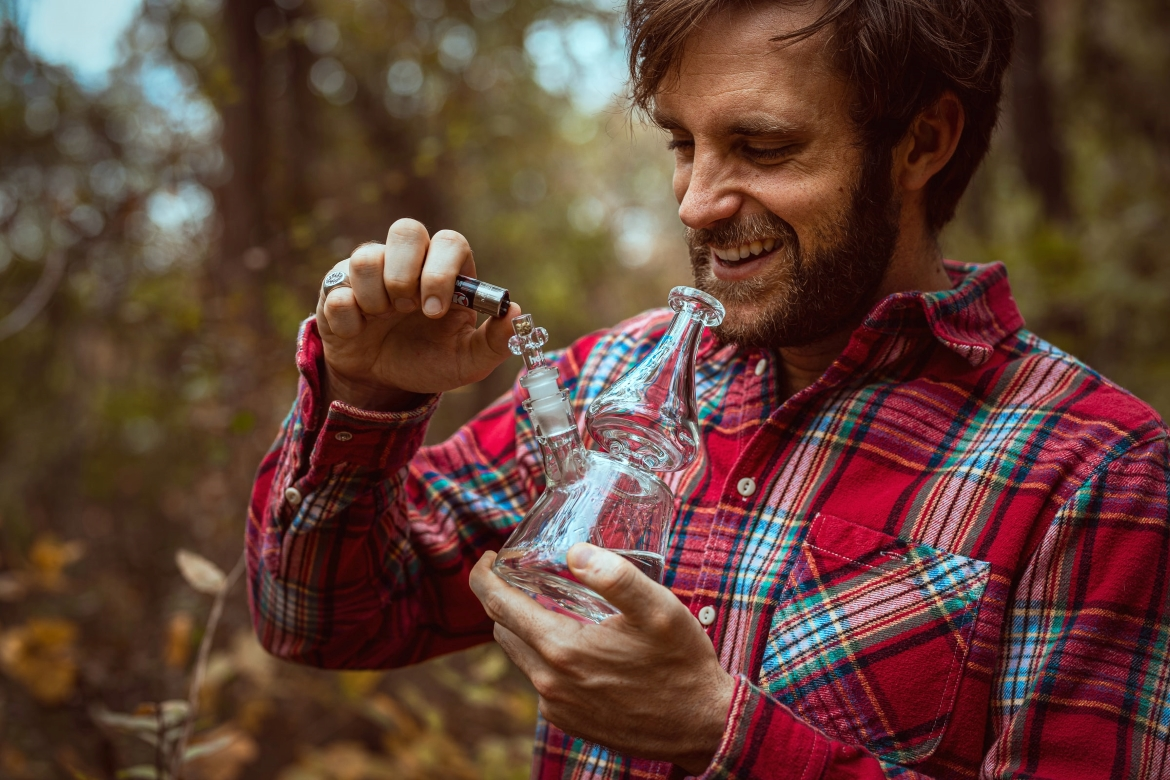 A man in a plaid shirt stands in the forest and enjoys hemp flower from a bong to help his anxiety.