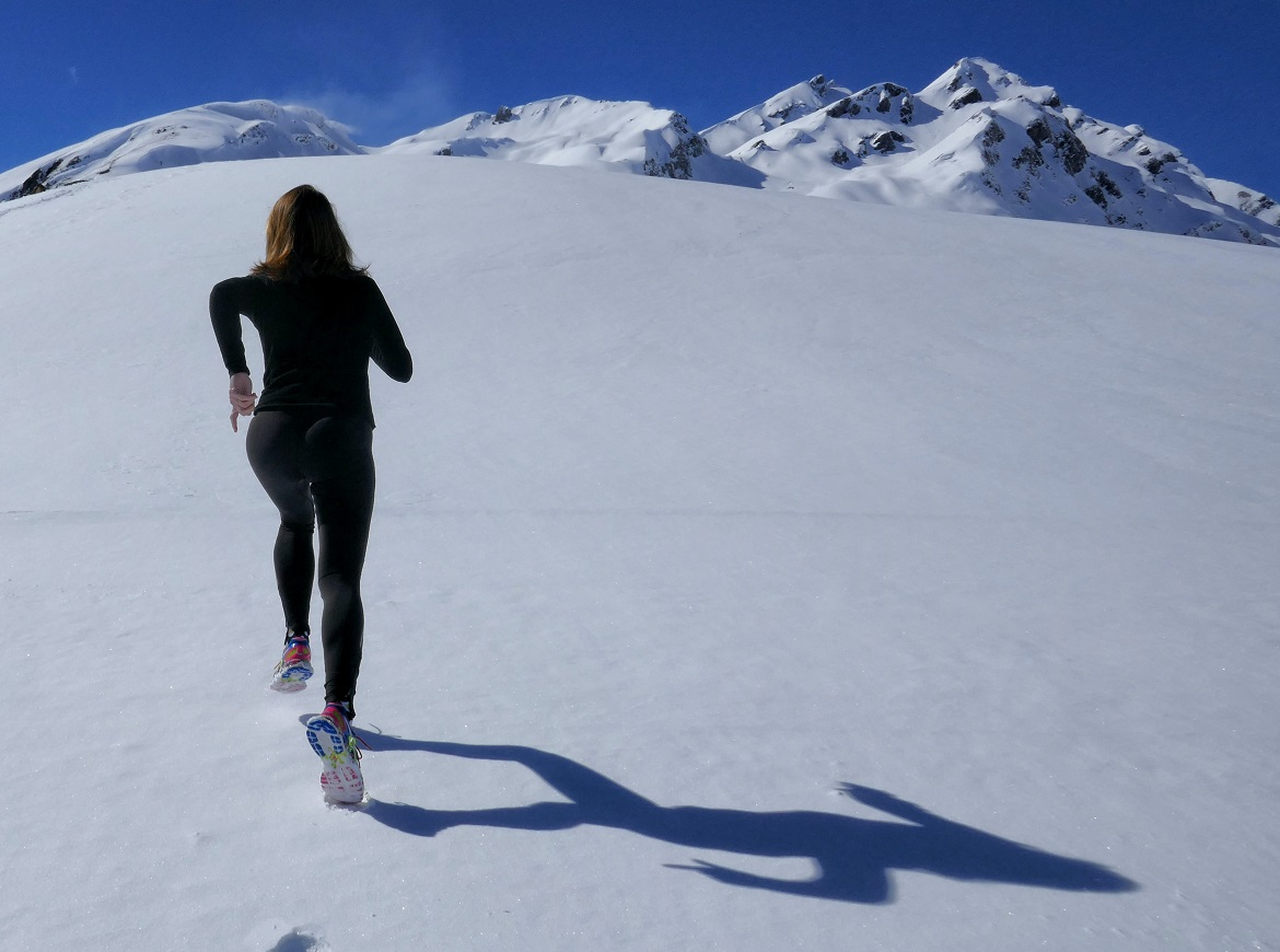 A woman running up a snowy mountain