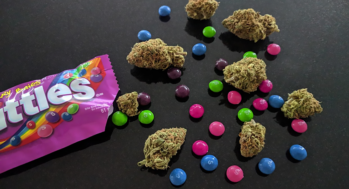 Purple Skittles cannabis flower near some actual Skittles candy