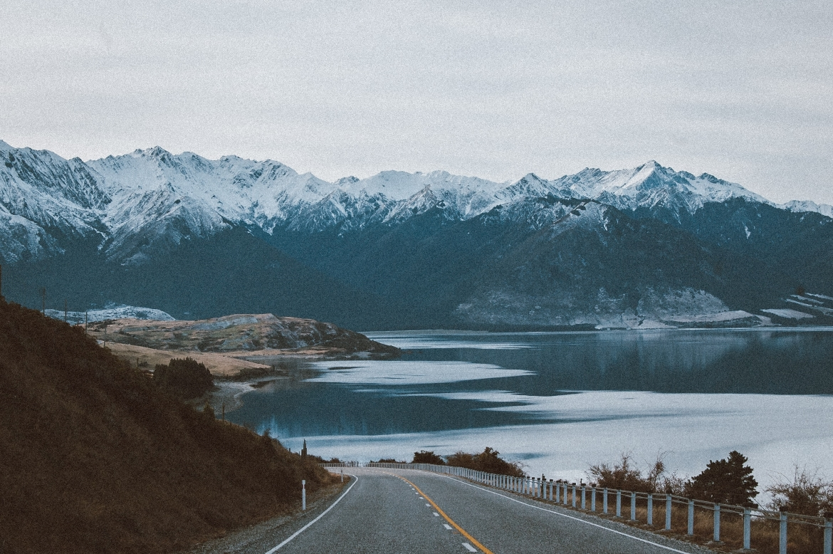 A road leads around a mountain side in Alaska. A large body of water and mountain peaks stand in the distance.