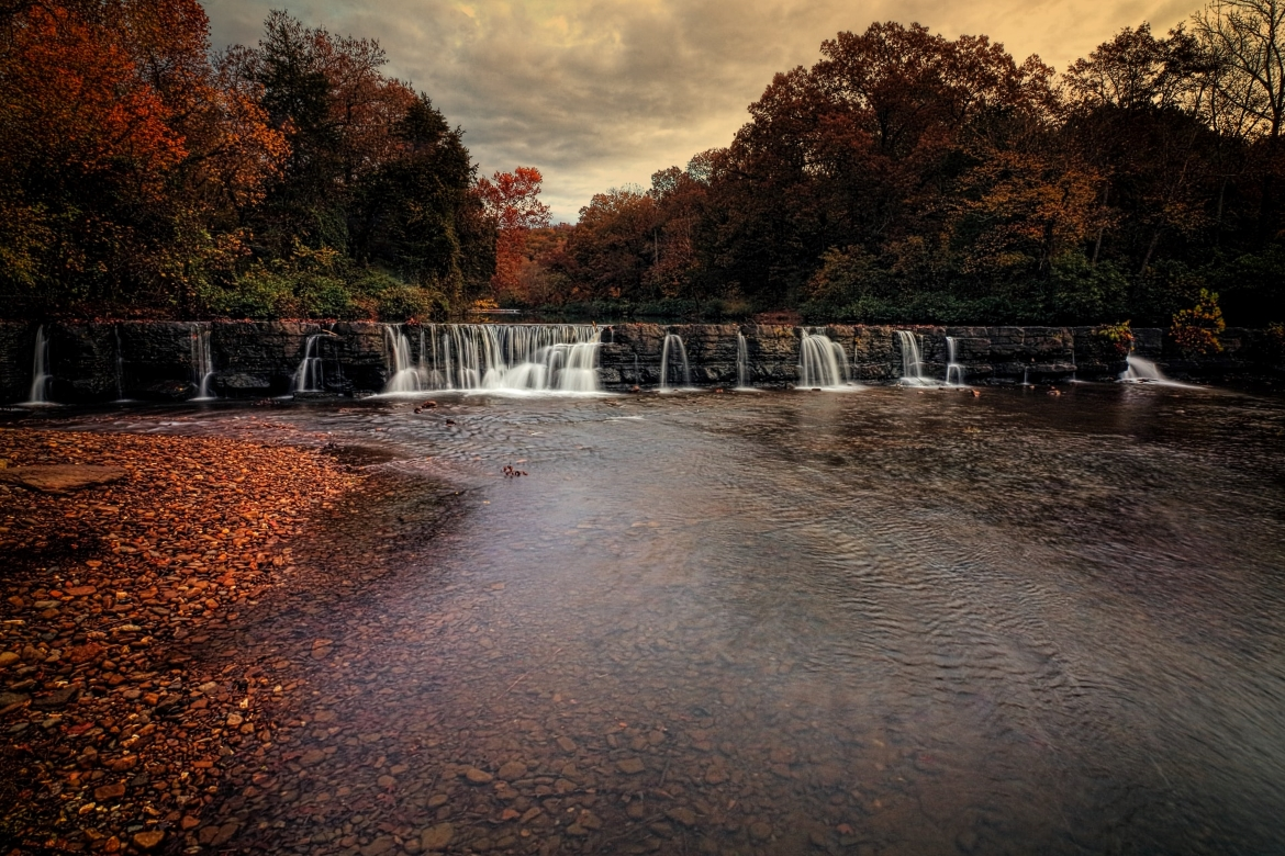 A beautiful water fall in Arkansas is surrounded by a red and orange forest in autumn