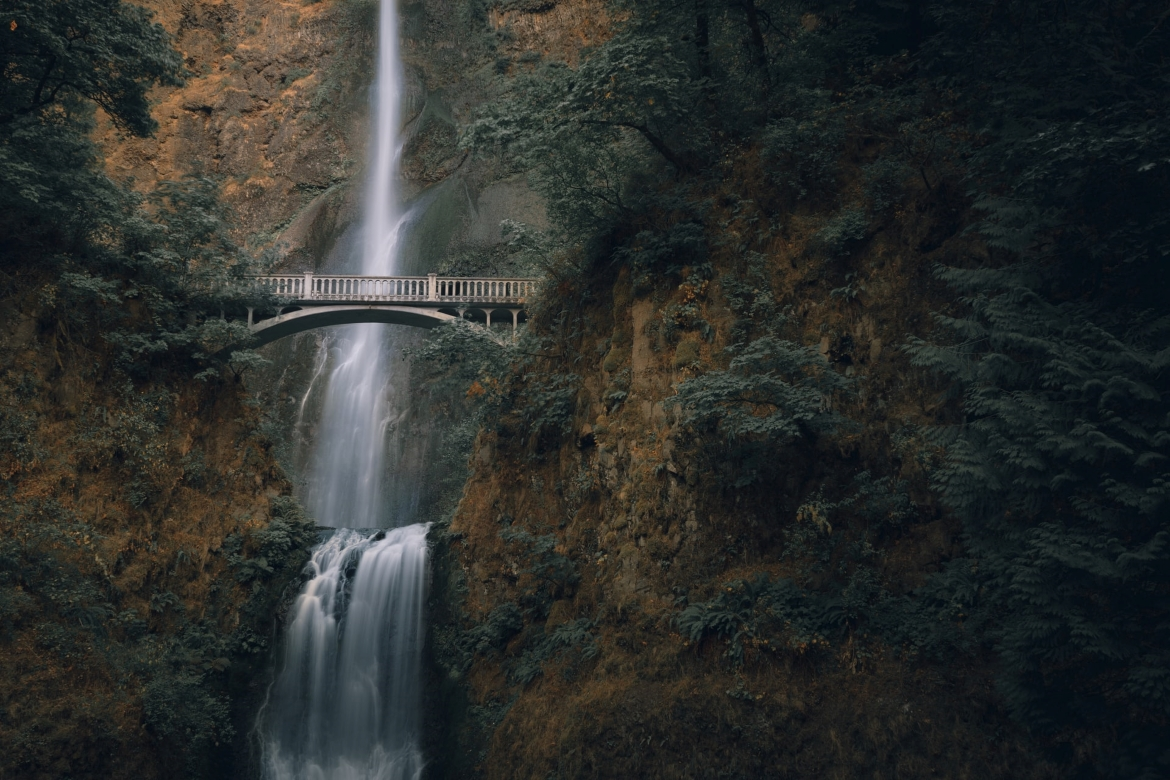 A beautiful bridge in Oregon, is over top of a cascading waterfall.