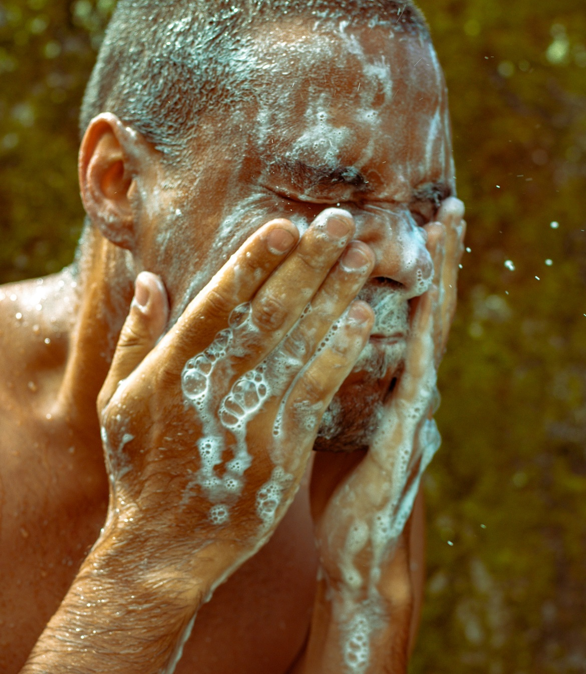 A man using hemp body wash on his face and hands
