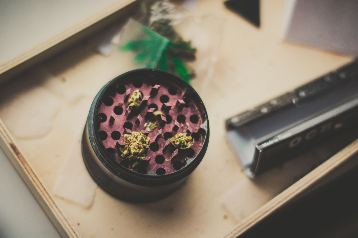 A cannabis grinder gilled with weed sits on a table beside rolling papers