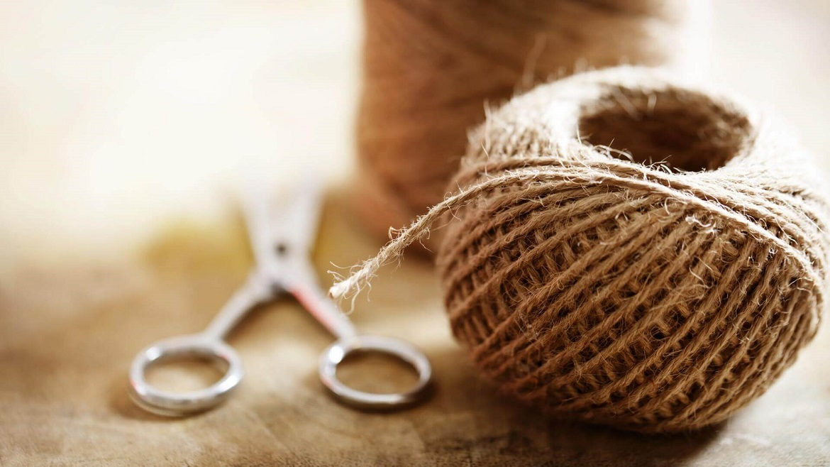A hemp wick roll is next to a pair of scissors on top of a table.