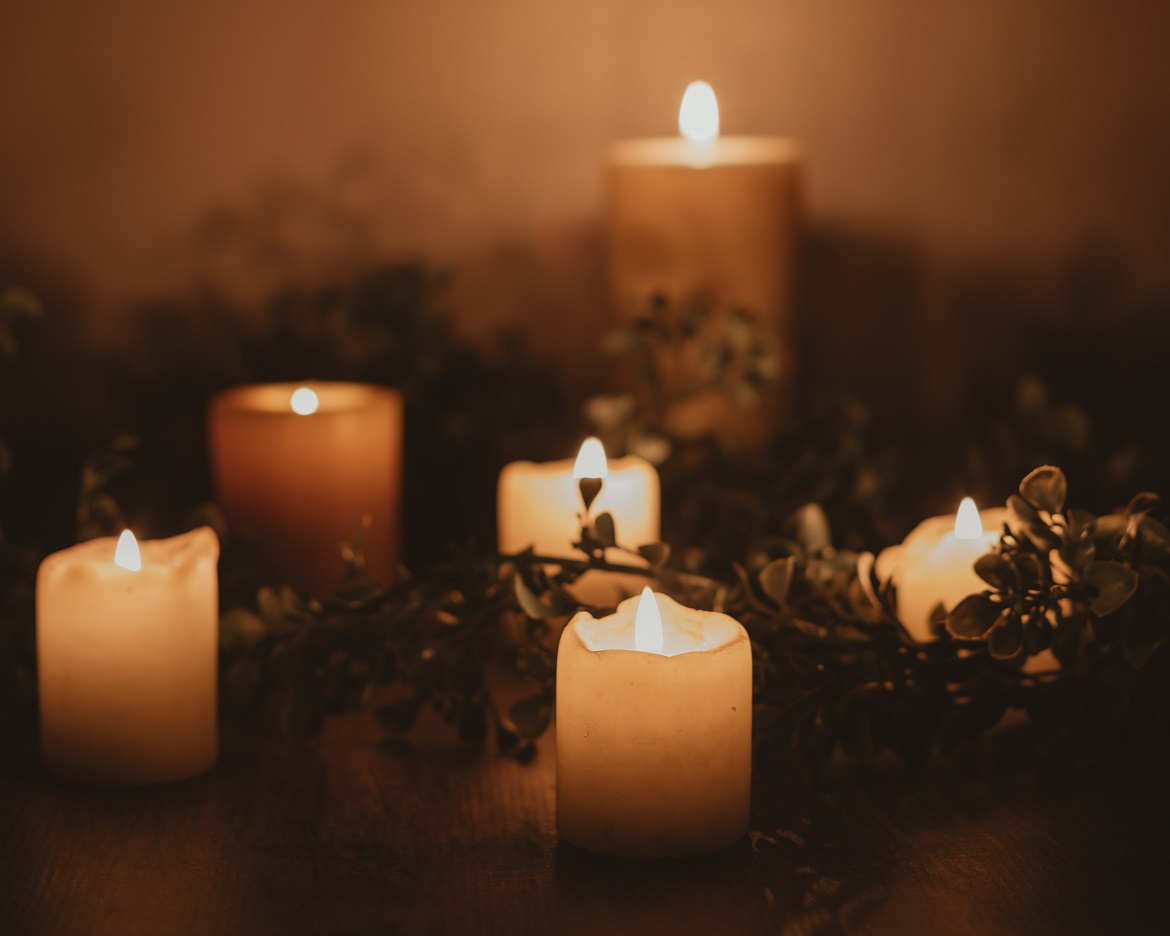 Six CBD candles are lit in the darkness surrounded by different herbs.