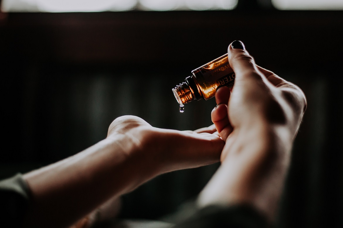 Person using CBD massage oil on their hand